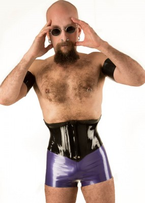 Man in woman's latex waist-cincher corset